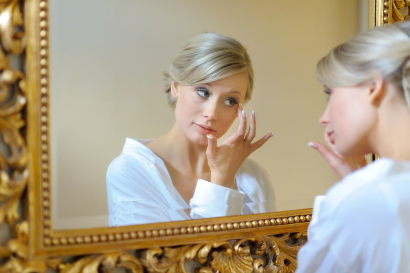 Bride looks in the mirror at Dunstable Hall