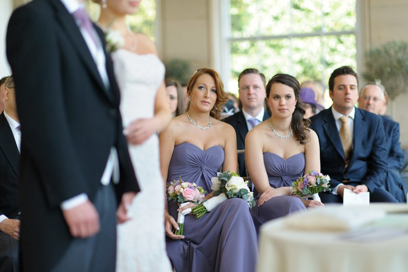Wedding photography: bridesmaids looking on.