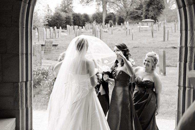 Bride arriving at Edensor church, bridesmaids help her with her veil.