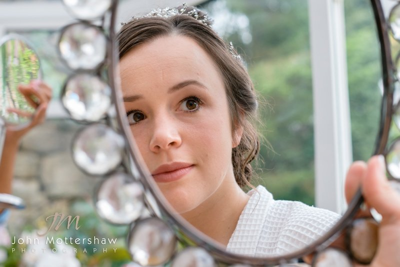 Wedding photography: preparation shot of the bride looking in the mirror