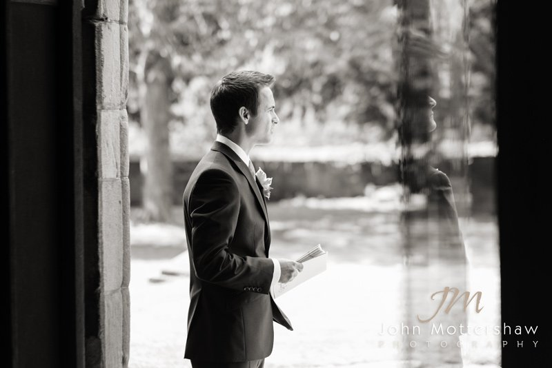 Groomsman at the church doorway. Wedding photographers in Derbyshire