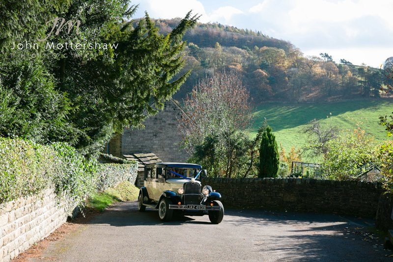 Wedding photography in Derbyshire. Wedding car arrives at Hathersage Church in the Derbyshire Peak District